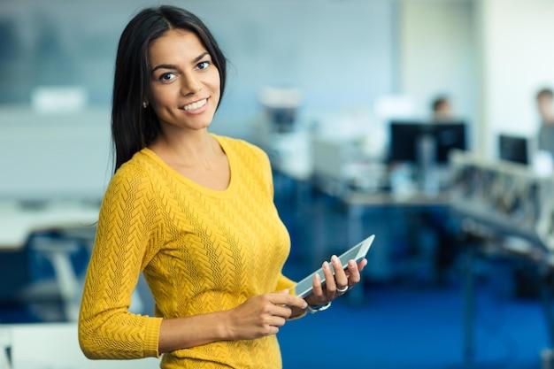 Портрет веселой повседневной бизнес-леди в свитере, стоящей с планшетным компьютером в офисе