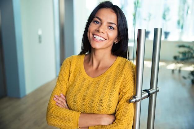 Портрет веселой повседневной бизнес-леди, стоящей со сложенными руками в офисе