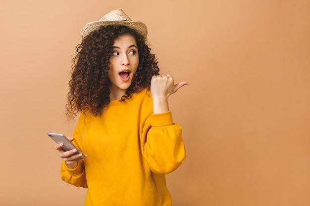 ベージュ色の背景に分離された携帯電話を押しながら人差し指を離れて陽気なカジュアルな巻き毛学生少女の肖像画。