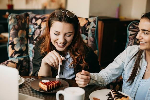 Портрет веселой кавказской женщины, сидящей в кафе, рассказывающей со своим другом, пока она ест чизкейк и пьет кофе.