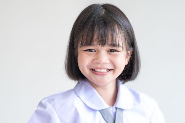 Портрет жизнерадостного ребенка-студента, изолированного на белом фоне, улыбается и смотрит в камеру. снова в школу stock photo