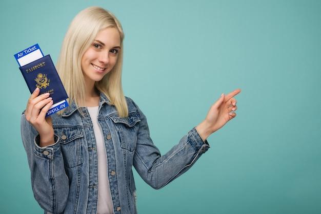 チケットとパスポートを示し、青い背景で隔離のコピーspaseを指している陽気なかわいいアメリカの女の子の旅行者の肖像画