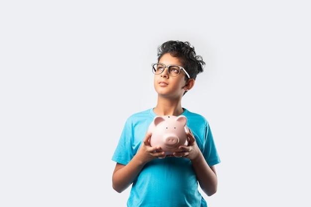 흰 벽에 격리된 책이 있는 돼지 저금통을 들고 있는 밝고 귀여운 인도 아시아 아이의 초상화