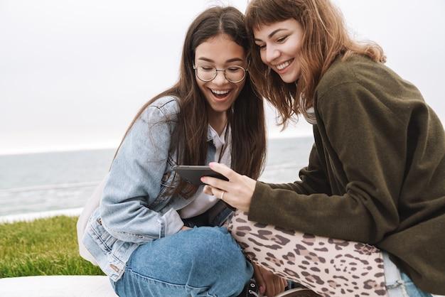Портрет веселых эмоциональных молодых симпатичных друзей женщин-студентов, сидящих на открытом воздухе с помощью мобильного телефона.