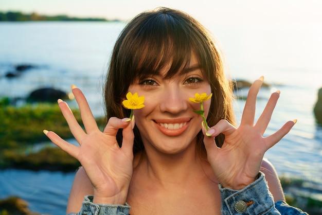 彼女の顔の近くに花を持って、水を背景に陽気なヨーロッパの若い女性の肖像画。自然化粧品のコンセプト