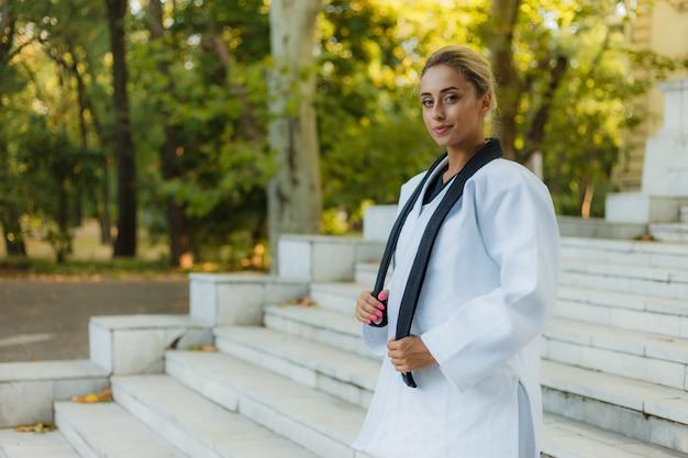 Портрет жизнерадостной женщины-бойца в белых кимоно с черным поясом на открытом воздухе