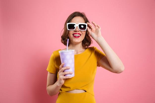 Портрет жизнерадостной девушки в солнечных очках держа чашку