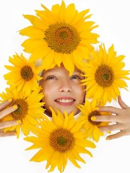 黄色いひまわりの陽気な女の子の肖像画。