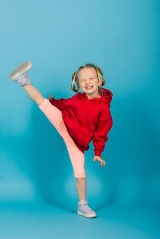 Портрет веселой девушки прыгает и танцует на фоне студии
