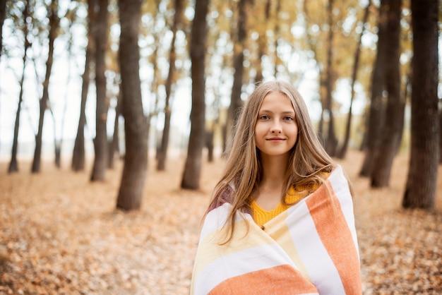 밝은 가을 색으로 가득한 공원을 걷는 따뜻한 격자 무늬에 싸인 쾌활한 소녀의 초상화