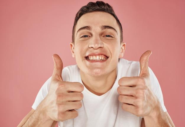 Портрет веселого парня на розовом фоне обрезанный вид белой футболки эмоции