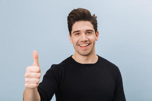 Портрет веселого красивого молодого человека, стоящего изолированно на синем, показывая большие пальцы руки вверх