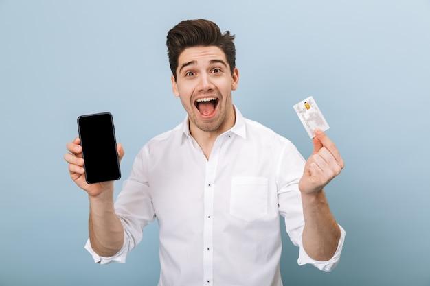 Портрет веселого красивого молодого человека, стоящего изолированно на синем, держащего кредитную карту и использующего мобильный телефон