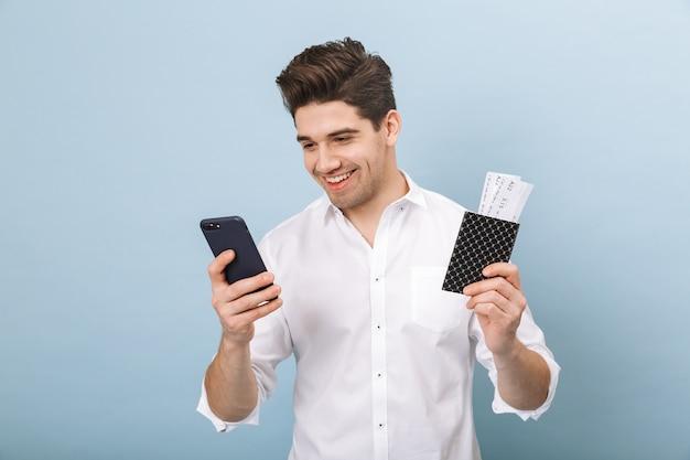 Портрет веселого красивого молодого человека, стоящего изолированно на синем, с паспортом и билетами на самолет и использующего мобильный телефон
