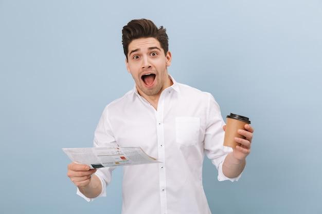 Портрет веселого красивого молодого человека, стоящего изолированно на синем, с чашкой кофе на вынос и читающего газету