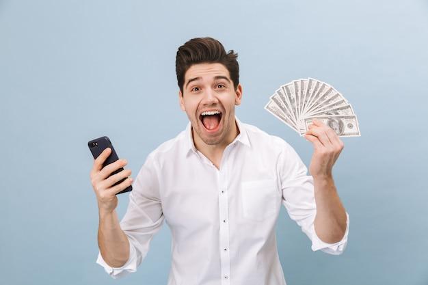 쾌활한 잘 생긴 젊은 남자가 파란색에 고립 된 서, 휴대 전화를 들고 돈 지폐를 보여주는 초상화