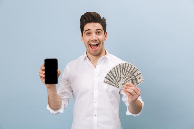 쾌활한 잘 생긴 젊은 남자가 파란색에 고립 된 서, 돈 지폐를 보여주는, 빈 화면 휴대 전화를 보여주는 초상화
