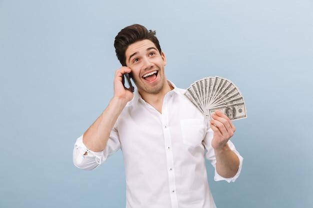 쾌활한 잘 생긴 젊은 남자가 파란색에 고립 된 서, 돈 지폐를 보여주는, 휴대 전화에 대 한 얘기의 초상화