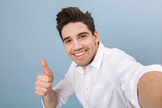 Портрет веселого красивого молодого человека, стоящего изолированно на синем и делающего селфи