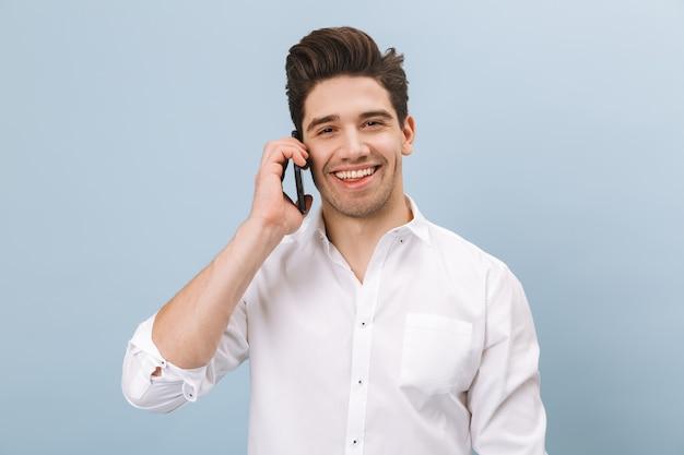 青で孤立して立っている、携帯電話で話している陽気なハンサムな若い男の肖像画