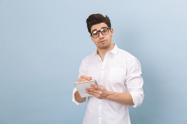 파란색에 고립 된 서 안경을 쓰고 쾌활한 잘 생긴 젊은 남자의 초상화, 메모