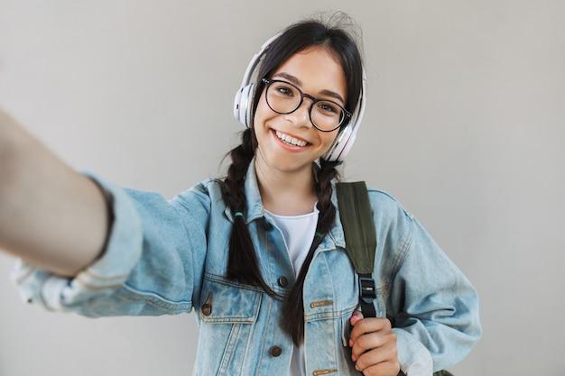 ヘッドフォンで音楽を聴いて灰色の壁の上に分離された眼鏡を身に着けているデニムジャケットの陽気な幸せな美しい少女の肖像画は、カメラで自分撮りを取ります。