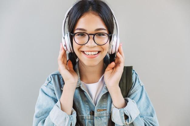ヘッドフォンで音楽を聴いて灰色の壁の上に隔離された眼鏡を身に着けているデニムジャケットで陽気な幸せな美しい少女の肖像画。