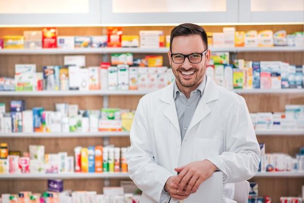 Портрет жизнерадостного работника здравоохранения в белом пальто на фармацевтическом магазине.