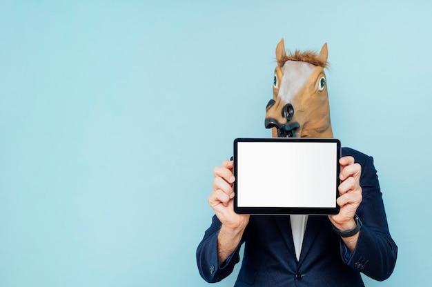 青い背景で隔離のタブレットと陽気な馬の肖像画。