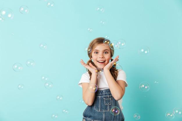 파란 벽에 격리된 쾌활한 어린 소녀의 초상화, 비누방울을 불고, 즐겁게