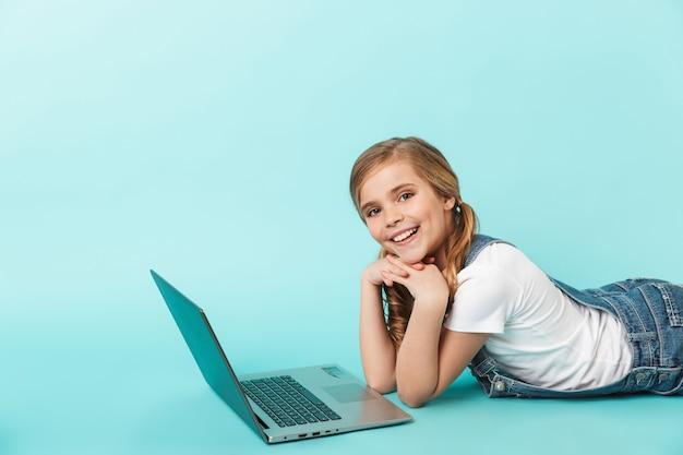 ラップトップコンピューターで勉強して、青い壁に隔離された陽気な少女の肖像画
