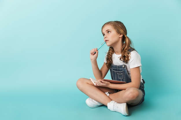 ノートに書いている青い壁に隔離された陽気な少女の肖像画