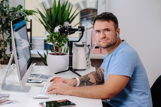 昼間の彼の仕事で陽気な男性サラリーマンの肖像画。白人の男は、テーブルに座って、デスクトップコンピューターでカメラを見ているポーズをとる。