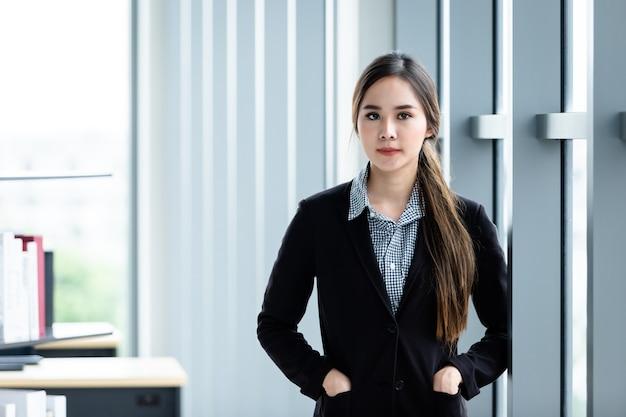 사무실 배경에서 쾌활한 성숙한 아시아 여성 사업가의 초상화, 비즈니스는 대담하고 성공적인 개념을 표현했습니다.