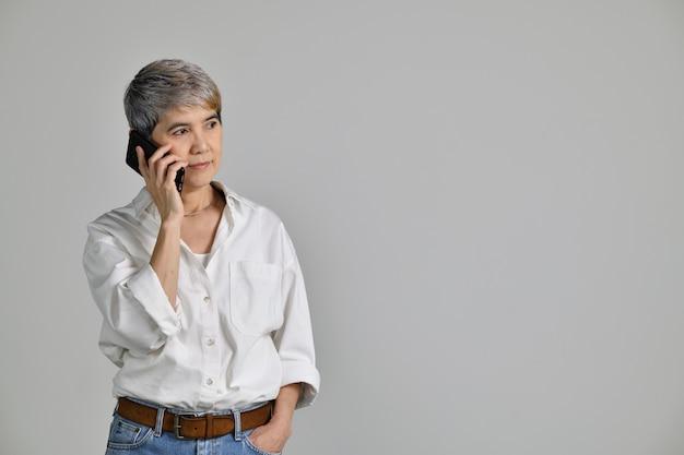 흰색 배경 위에 격리된 스마트폰으로 이야기하는 쾌활한 중년 아시아 사업가의 초상화