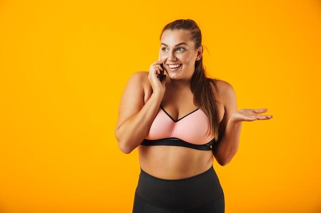 Портрет веселой женщины фитнеса с избыточным весом в спортивной одежде, стоящей изолированно над желтой стеной и разговаривающей по мобильному телефону