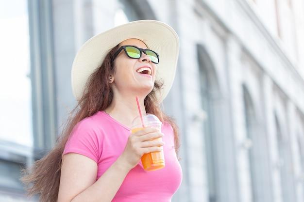 화창한 여름날 도시를 산책하는 모자와 안경을 쓴 쾌활한 긍정적인 젊은 여성의 초상화. 평온한 분위기의 개념입니다.