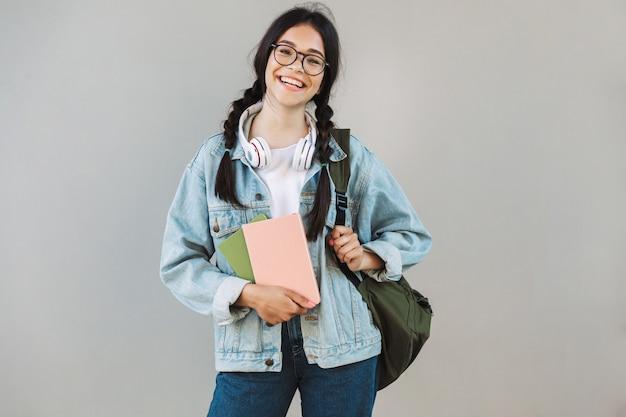 バックパックを保持し、本を保持している灰色の壁の上に分離されたカメラを見ている眼鏡をかけているデニムジャケットの陽気なかわいい女の子の肖像画。