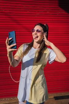 Портрет веселой красивой девушки, слушающей музыку в наушниках, стоя и принимая селфи.