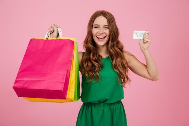 買い物袋を示す陽気なきれいな女性の肖像画