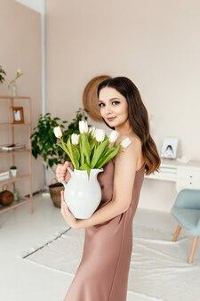 美しい新鮮な花と花瓶を保持している陽気なかなり若い女性の肖像画
