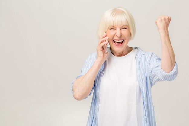 Портрет жизнерадостной старшей женщины показывать победу изолированной над белой предпосылкой. с помощью телефона.