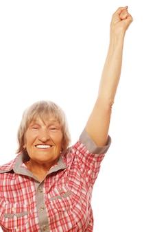Портрет веселой старшей женщины, показывающей победу на белом фоне