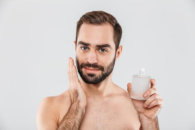 Портрет веселого бородатого мужчины без рубашки, применяющего лосьон после бритья, изолированный на белом