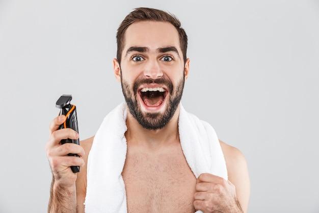 Портрет веселого бородатого мужчины без рубашки, показывающего электрическую бритву, изолированную на белом