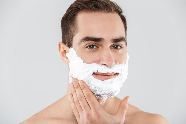 Портрет веселого бородатого мужчины без рубашки, стоящего изолированно над белой, лицо покрыто пеной для бритья
