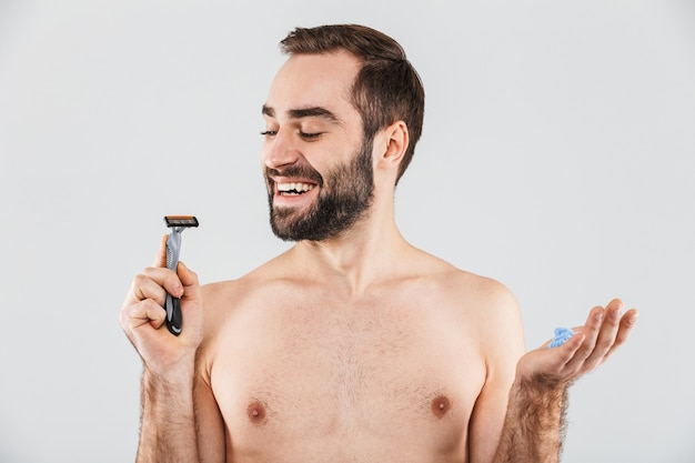 Портрет веселого бородатого мужчины без рубашки, стоящего изолированно над белой и держащего бритву