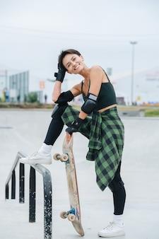 한 발로 난간을 밟고 보드에 기대어 있는 쾌활한 스케이팅 여자의 초상화. 배경에서 흐리게 도시입니다.