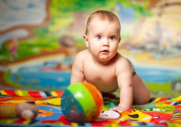 Портрет веселой улыбающейся шестимесячной девочки, играющей в детской с развивающими игрушками