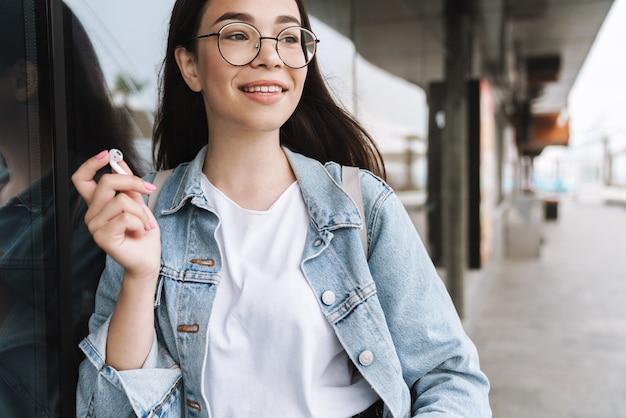 Портрет веселой улыбающейся молодой красивой студентки в очках, идущей на свежем воздухе, отдыхая, слушая музыку в наушниках